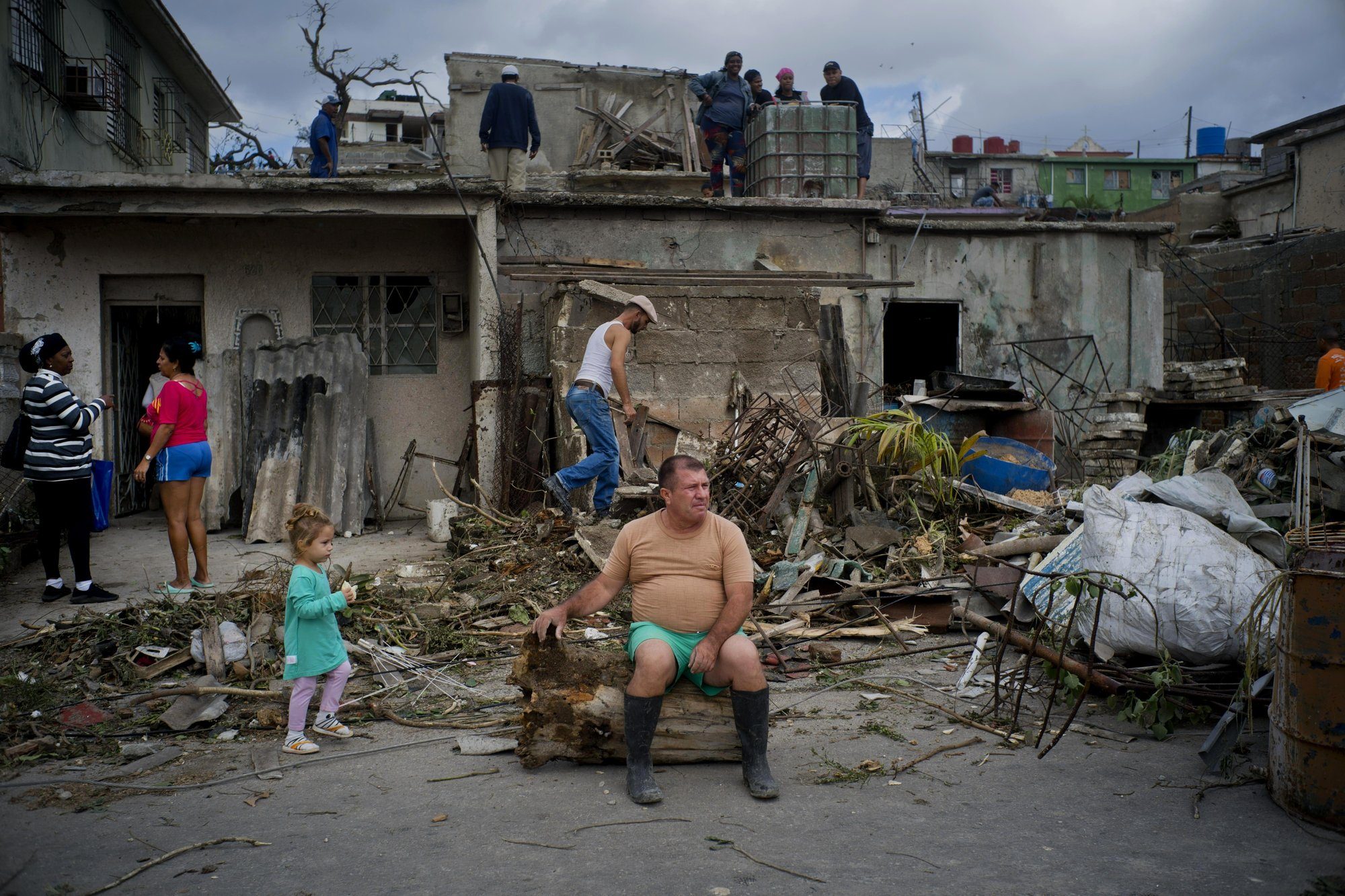 A man rests on the trunk of a tree that was toppled by a tornado, as he takes a moment to rest from removing rubble from his home in Regla, Cuba, on Monday, Jan. 28, 2019. Photo: AP