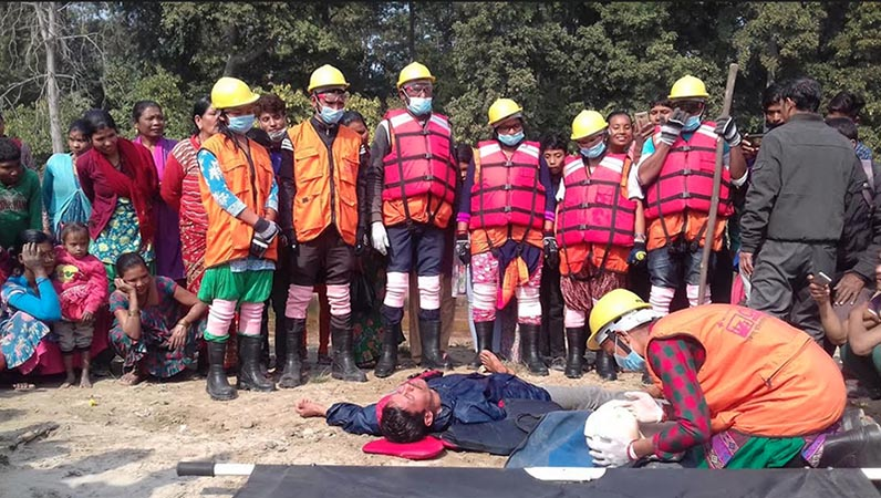 Locals of Damauliya village watching a man rescuing a victim posing unconscious man in a disaster response drill conducted by the members of Nepal Red Cross Society (NRCS) branch, on the bank of Shivaganga River, in Dhangadhi Sub-metropolitan City-17 of Kailali district, on Monday, January 21, 2019. Photo: Tekendra Deuba/THT