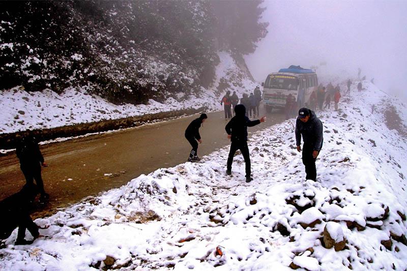 A bus awaits its passenger as they play snow along the road in Dolakha, on Friday, January 25, 2019. Photo: Gokaran Bhandari
