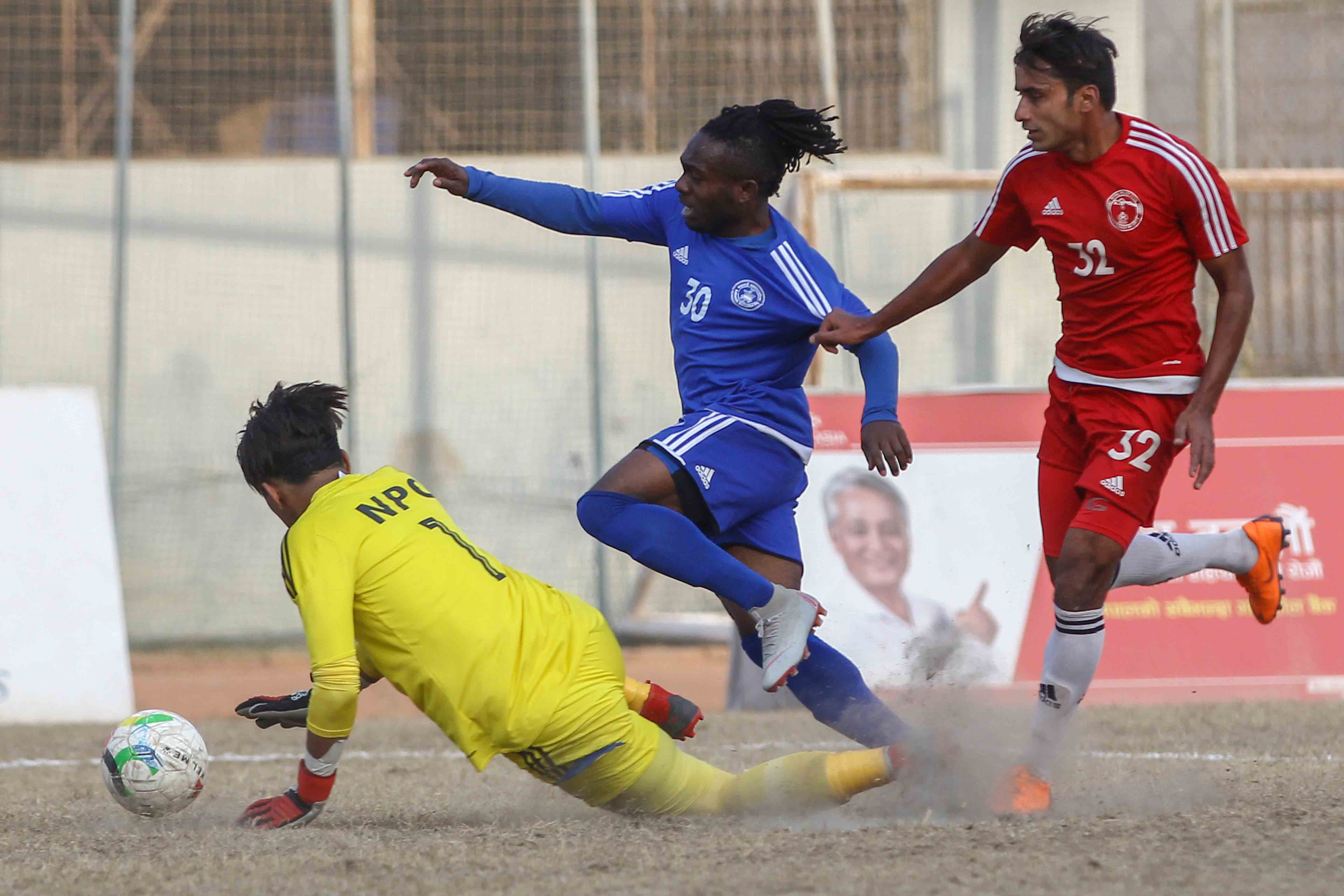 Victor Amobie (centre) of SYC vies with NPC goalkeeper Arpan Karki and Ajit Bhandari during their Pulsar Martyrs Memorial A Division League match in Kathmandu on Saturday. Photo: THT