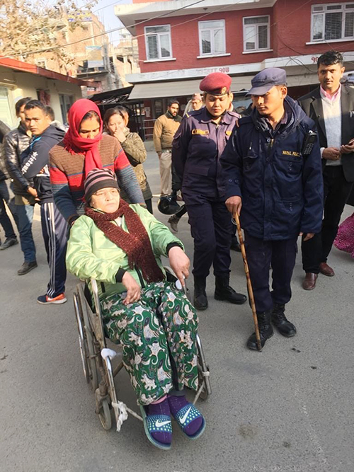 Ganga Maya Adhikari on a wheelchair, accompanied by police in civvies and uniform, at District Administration Office, in Kathmandu, on January 1, 2019. She applied to get her first passport. Photo: Ujjwal Satyal/THT