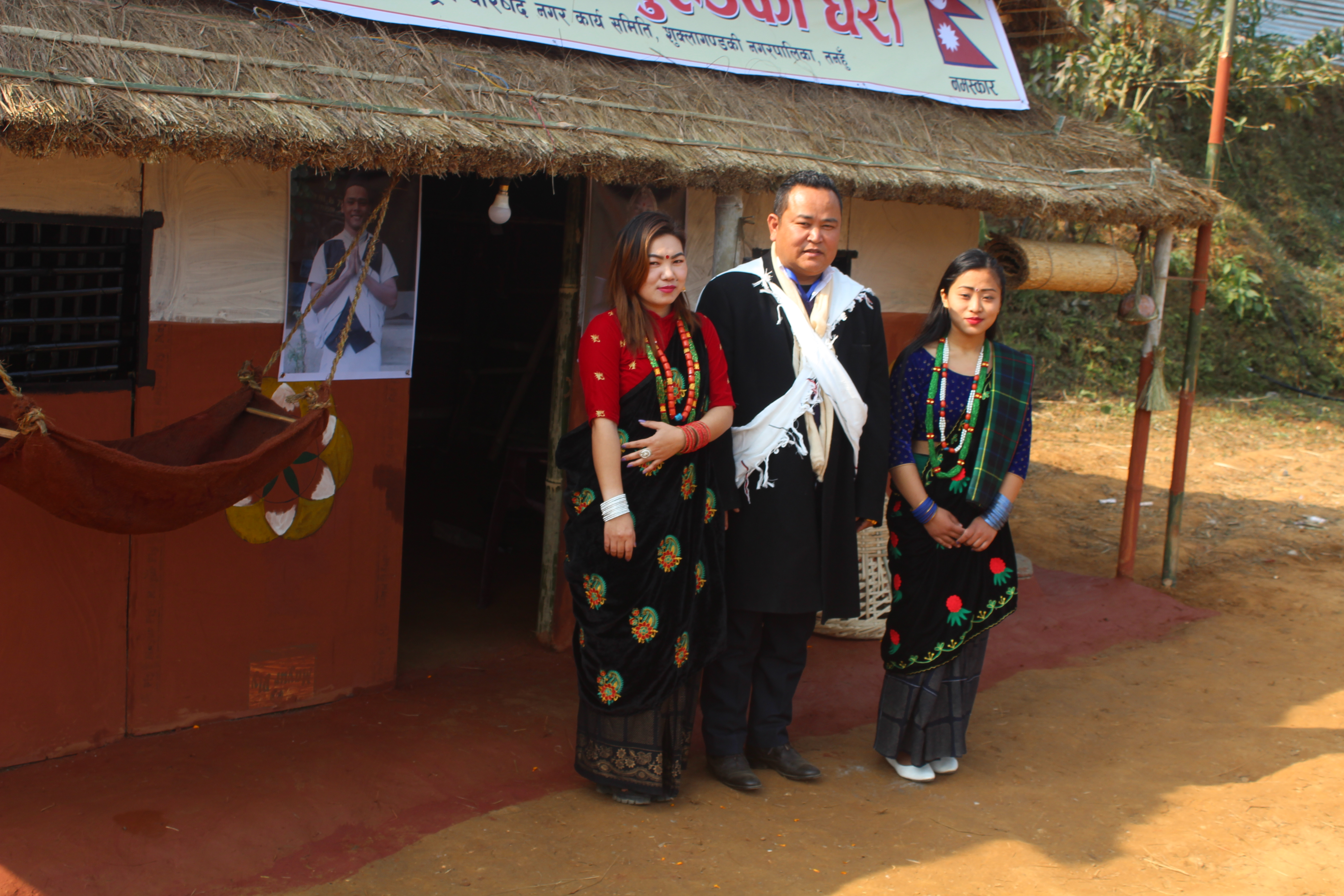Visitors in Gurung traditional attire pose for a photo in front of model typical Gurung house at Shukla Gandaki Cultural Festival organised by Nepal Federation of Indigenous Nationalities Council Municipal Working Committee, Shukla Gandaki, in khairenitar, Tanahun district, on Friday, January 11, 2019. Photo: THT