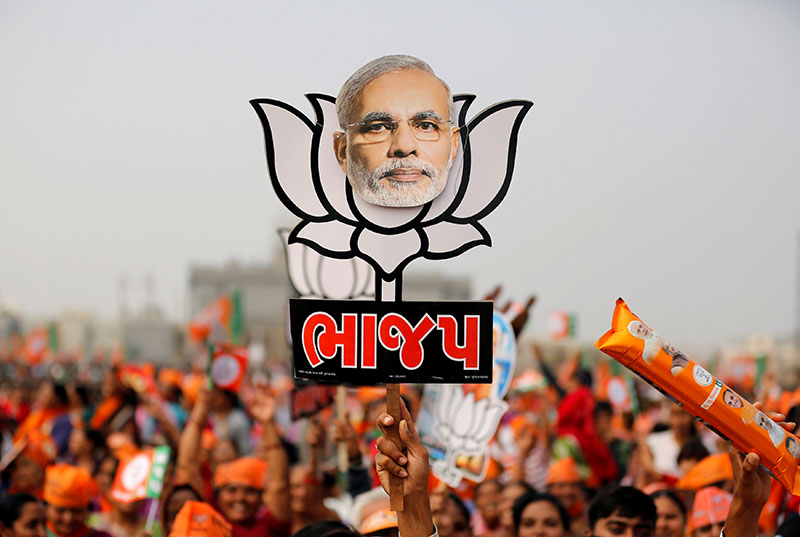 FILE -  A supporter holds up a cut-out of a lotus, the election symbol of India's ruling Bharatiya Janata party (BJP), with an image of Prime Minister Narendra Modi during a campaign meeting addressed by Modi ahead of Gujarat state assembly election in Kalol on the outskirts of Ahmedabad, India, December 8, 2017. Photo: Reuters
