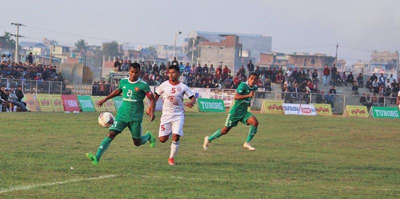 Tribhuwan Army Club skipper Bharat Khawas (left) dribbles the ball past Mechi Netralaya Kakarvitta Football Training Centre player during their Madan Bhandari Memorial Itahari Gold Cup match in Sunsari on Wednesday. Photo: THT