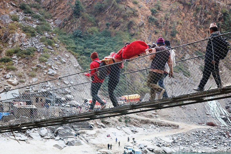 Villagers carry a patient on strecher to a district hospital from a remote village in Kalikot district, on Tuesday, January 15, 2018. Photo: RSS