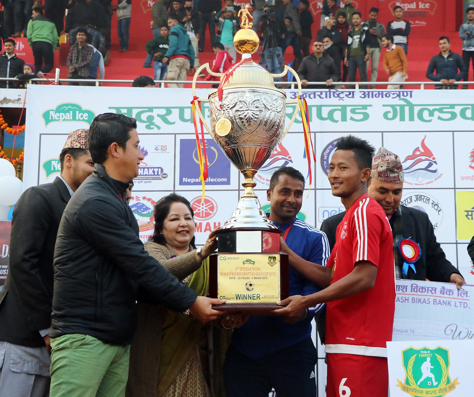 NPC players and officials receiving the Nepal Ice International nFarwest Khaptad Gold Cup trophy from social activist Arzu Rana Deuba in Dhangadhi on Saturday.