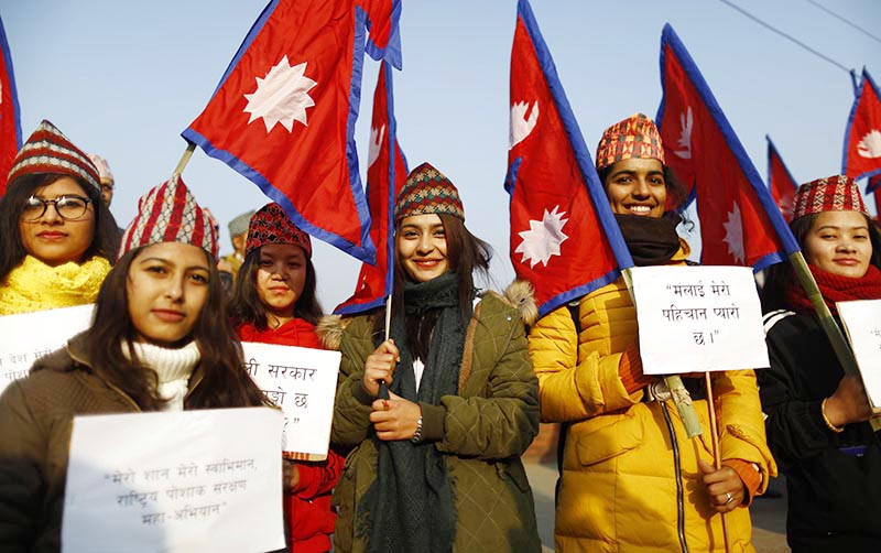 Women wearing 'Dhaka Topi', a traditional Nepali cap, holding placards and national flags take part in a rally organised to mark the National Costume Day in Maitighar Mandala, Kathmandu, on Tuesday, January 01, 2019. Photo: Skanda Gautam/THT