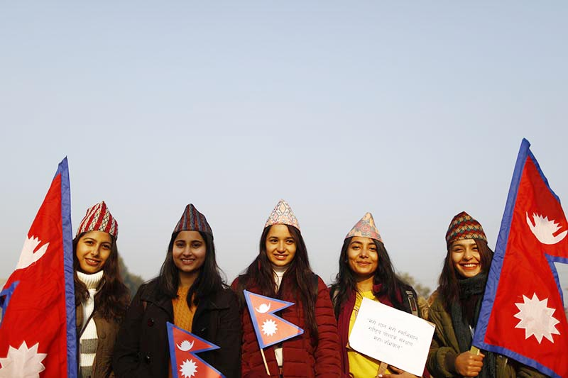 Women wearing 'Dhaka Topi' and holding placards ans national flags pose for photo while taking part in a rally otganised to mark the National Costume Day in Maitigahar Mandala, Kathmandu, on Tuesday, January 01, 2019. Photo: Skanda Gautam/THT