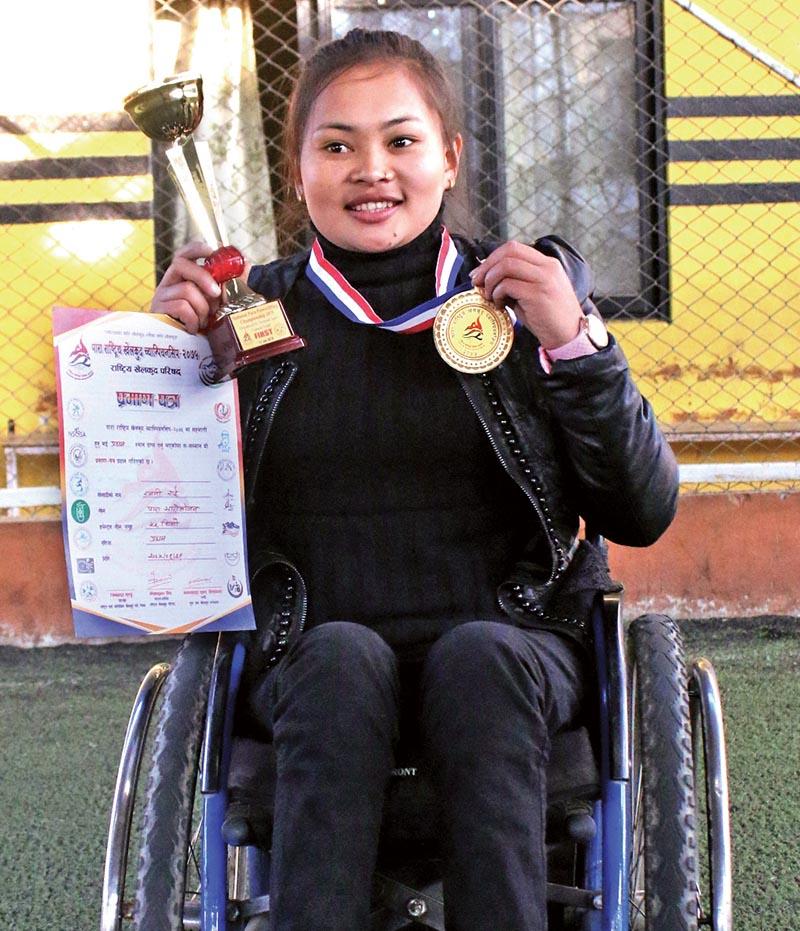 Rajani Rai displays her gold medal after winning the womenu2019s 55kg weight category in the National nPara-Weightlifting Championship in Kathmandu on Sunday. Rai lifted 40kg weight to win the gold ahead of Anu Rai (35kg) and Hem Kumari Rai (30kg). Photo: THT