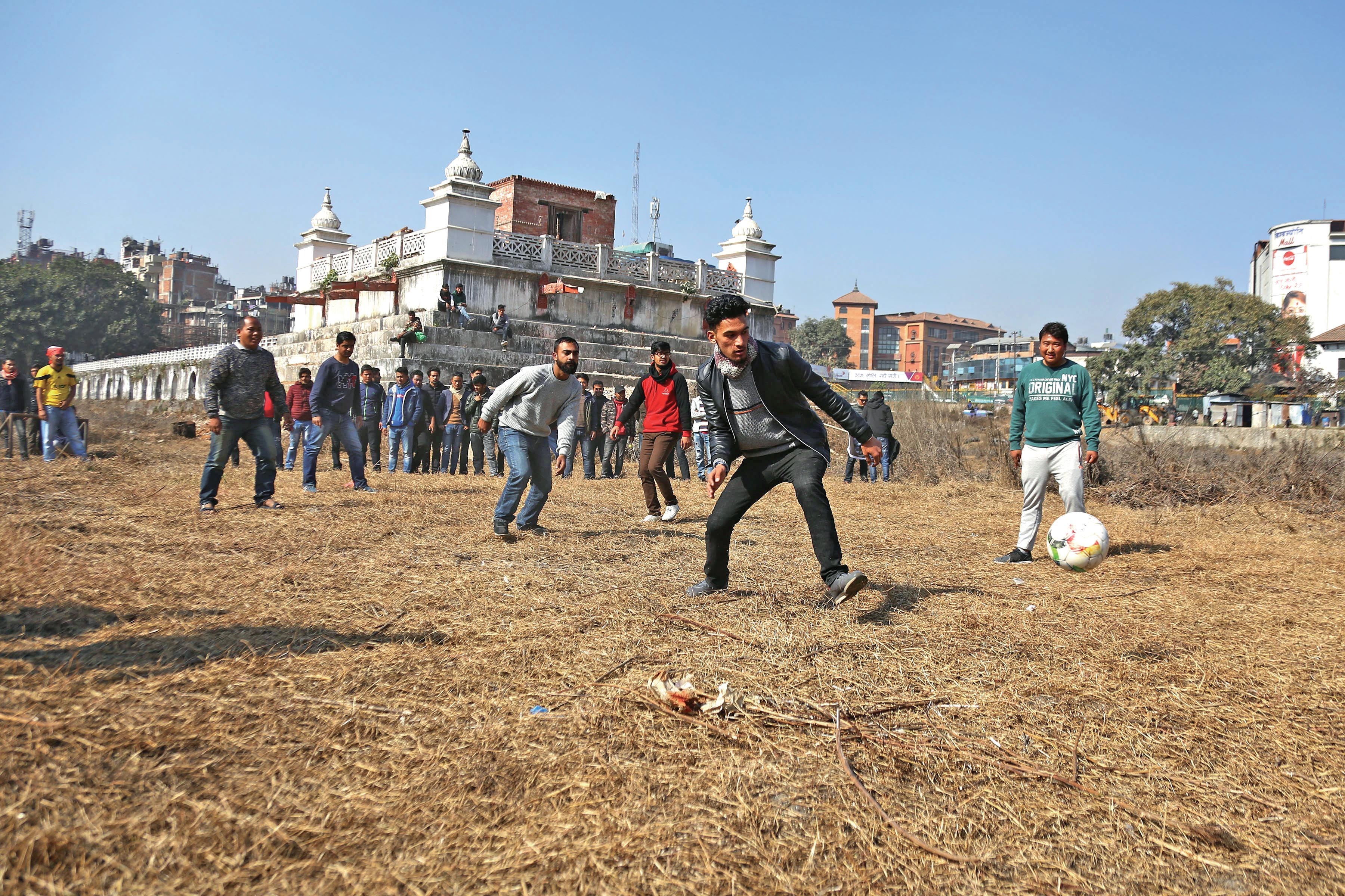 Students affiliated to Nepal Student Union playing football on the dried bed of Rani Pokhari in a symbolic protest against the delay in recontruction of the historic site, in Kathmandu, on Tuesday, January 8, 2019. Photo: THT