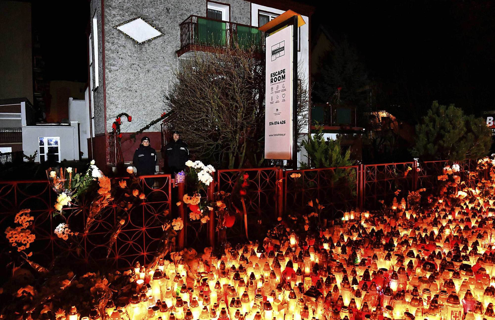 Lights, flowers and toys are left outside the escape room entertainment site where five teenage girls died in a fire last week, in Koszalin, northern Poland, on Sunday, Jan. 6, 2019. Photo: AP