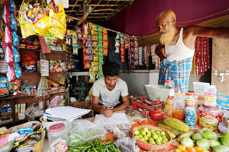FILE PHOTO: A man from the Rohingya community fills out an identification form, provided by local police, inside his shop at a camp in New Delhi, India October 4, 2018. Photo: Reuters