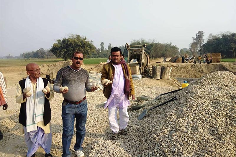 Locals including Province 2 Nepal Communist Party (NCP) member and youth leader Sambhu Sah Kanu show the pebbles considered substandard in the construciton of a bridge under Crystalised Urban Building Construction Project Parsa, in Gaur Municipality, Rautahat district, on Sunday, January 20, 2019. Photo: Prabhat Kumar Jha/THT