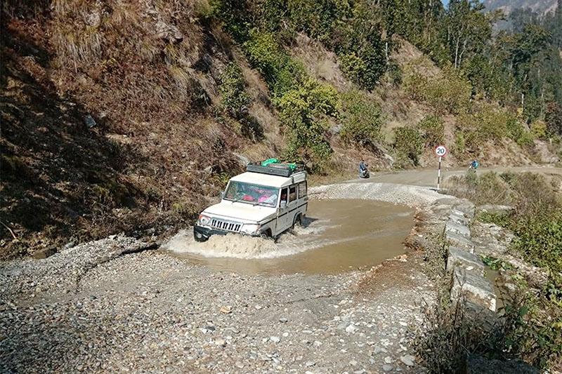 A jeep wades through puddle near Pasagada along Chinchu-Jajarkot road section in Bheri Municipality, on Tuesday, January 15, 2018. Photo: RSS