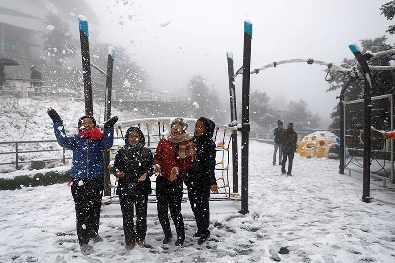People pose for a picture as they play with snow during a snowfall on Chandragiri Hills in Kathmandu, on Wednesday, January 23, 2019. Photo: Reuters