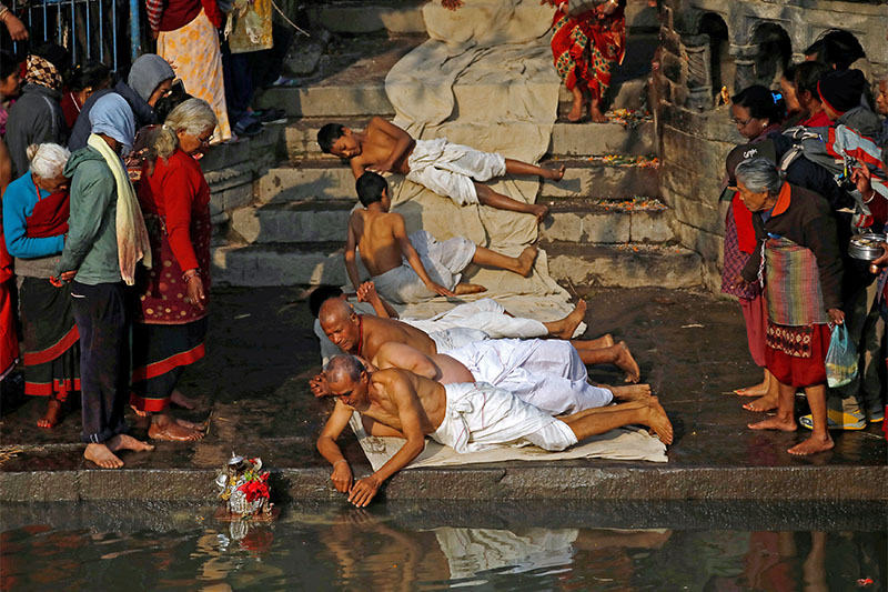 Devotees offer prayers by rolling on the ground during the Swasthani Brata Katha festival in Bhaktapur, Nepal on Monday, January 21, 2019. Photo: Reuters