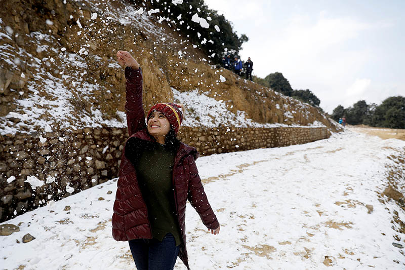 A woman plays with snow after a brief snowfall at Chandragiri Hills in Kathmandu, Nepal, on January 7, 2019. Photo: Reuters