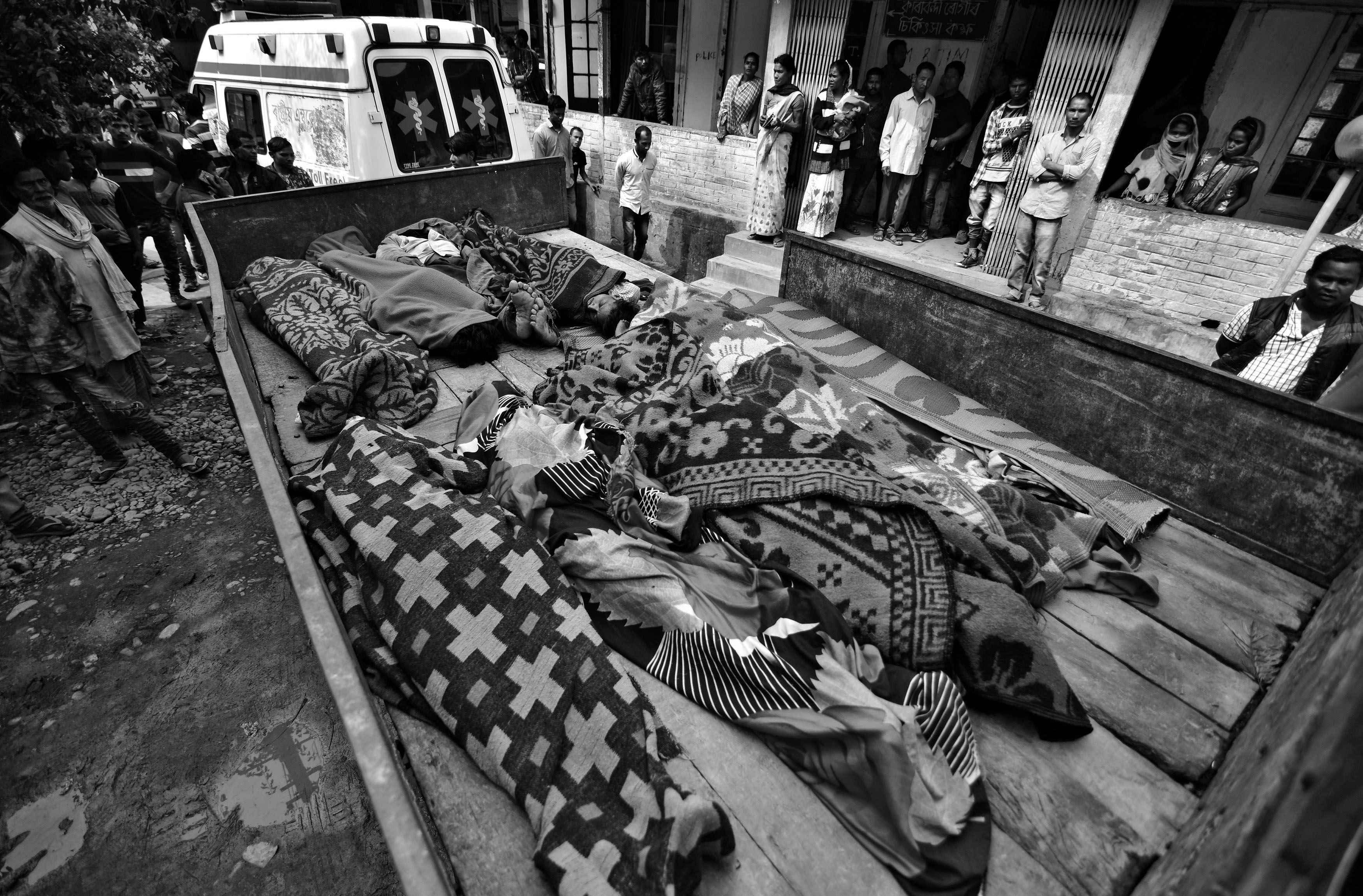 People look at the bodies of tea plantation workers, who died after consuming bootleg liquor, outside a government-run hospital in Golaghat in the northeastern state of Assam, India, February 23, 2019. REUTERS