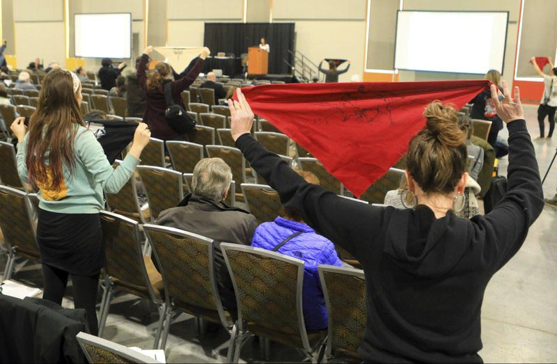 Protesters hold up flags during a public hearing on a draft environmental plan on proposed petroleum leasing within Alaska's Arctic National Wildlife Refuge in Anchorage, Alaska, on Monday, Feruary 11, 2019. Photo: AP