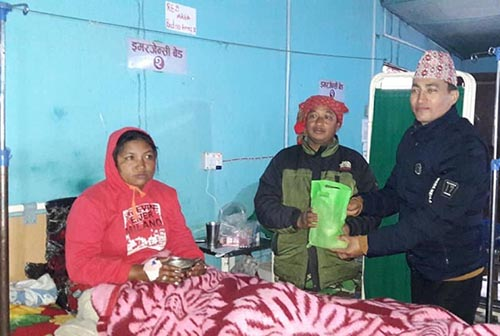 Bhojpur Industry and Commerce Association's General Secretary Nabin Pradhan hands over a package of fruits to patients at District Hospital in Bhojpur, on Monday, February 18, 2019. Photo: Niroj Koirala/THT