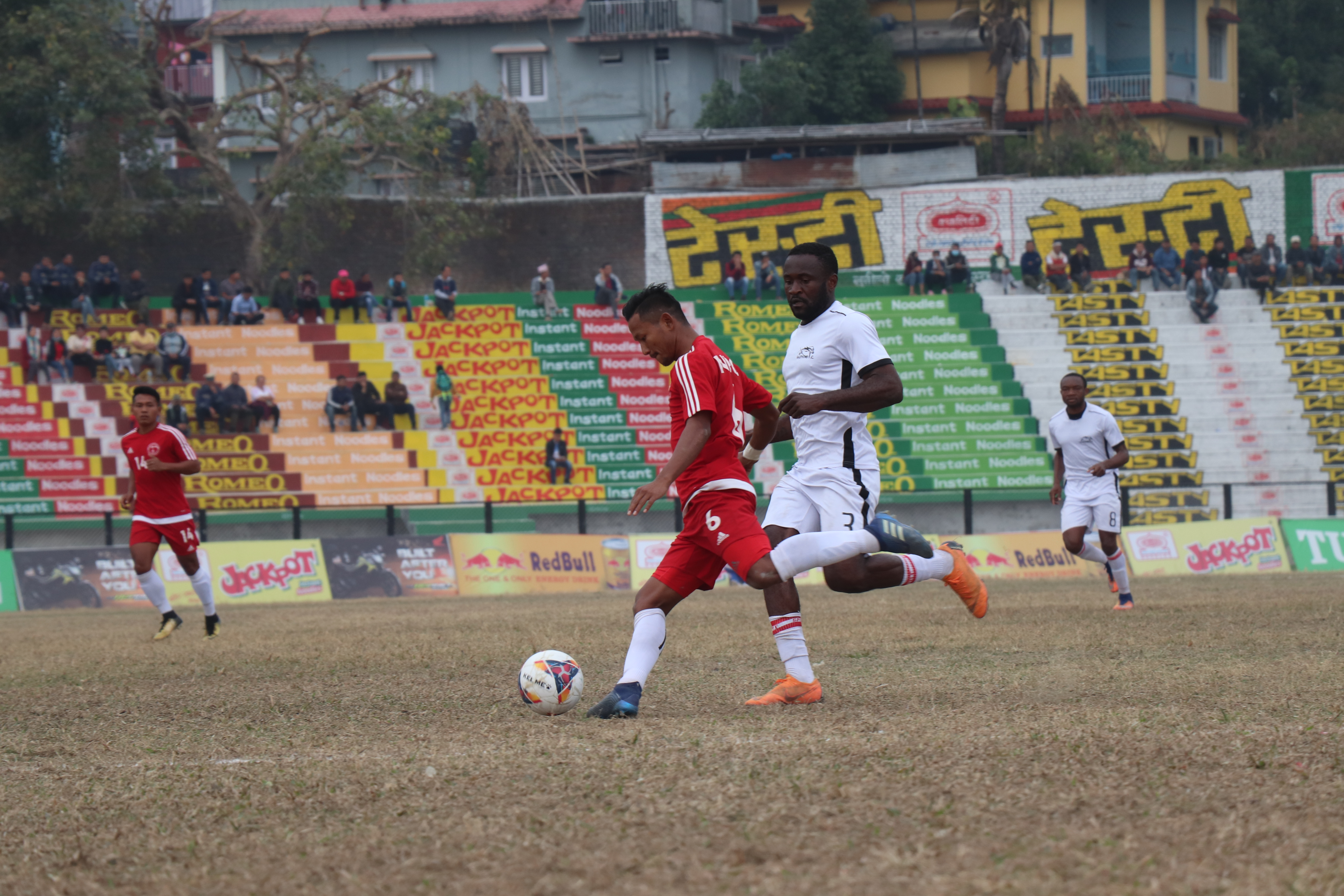 Players of Nepal Police Club (left) and Dauphins Family Club in action during their semi-final match of the 21st Budha Subba Red Bull Gold Cup at the Dharan Stadium in Sunsari on Friday. Photo: THT