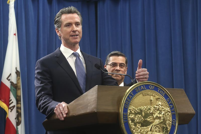 California Governor Gavin Newsom, left, flanked by Attorney General Xavier Becerra, right, answers a question concerning a  lawsuit the state will likely file against President Donald Trump over his emergency declaration to fund a wall on the U.S.-Mexico border Friday, February 15, 2019, in Sacramento, California.Photo: AP