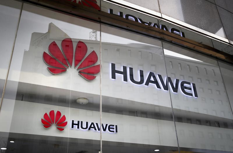 The logos of Huawei are displayed at its retail shop window reflecting the Ministry of Foreign Affairs office in Beijing,China , on this January 29, 2019. Photo: AP