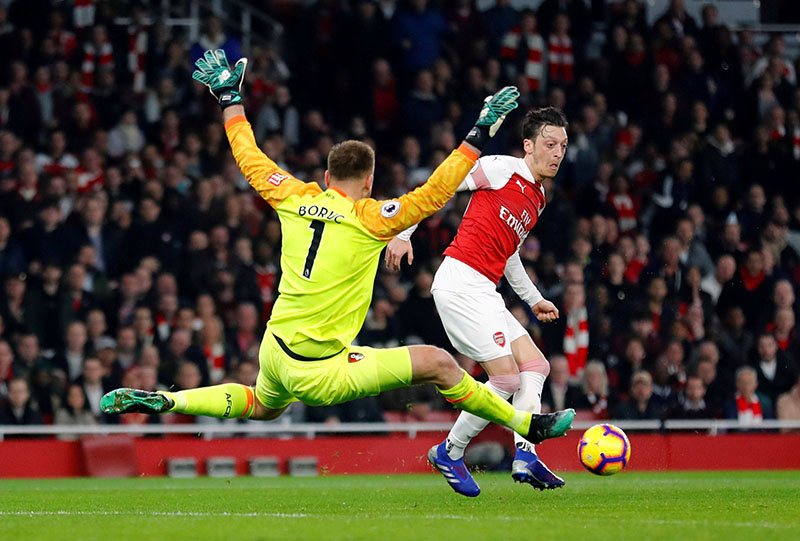 Arsenal's Mesut Ozil in action with Bournemouth's Artur Boruc during the Premier League match between Arsenal and AFC Bournemouth, at Emirates Stadium, in London, Britain, on February 27, 2019. Photo: Retuers