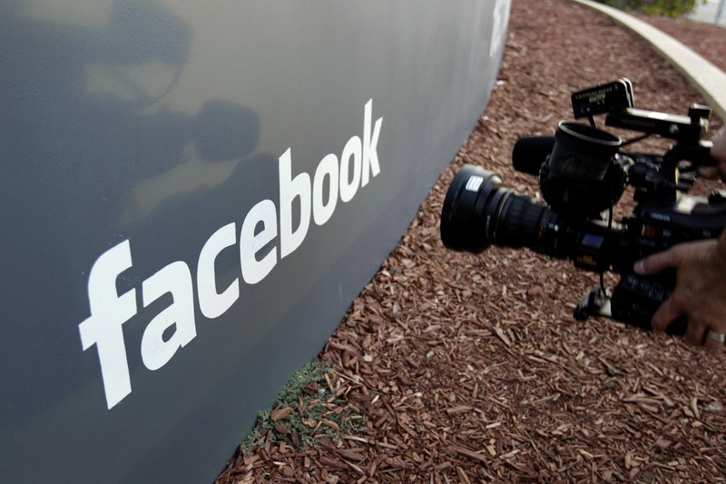 FILE - In this May 18, 2012, file photo a television photographer shoots the sign outside of Facebook headquarters in Menlo Park, California. Photo: AP