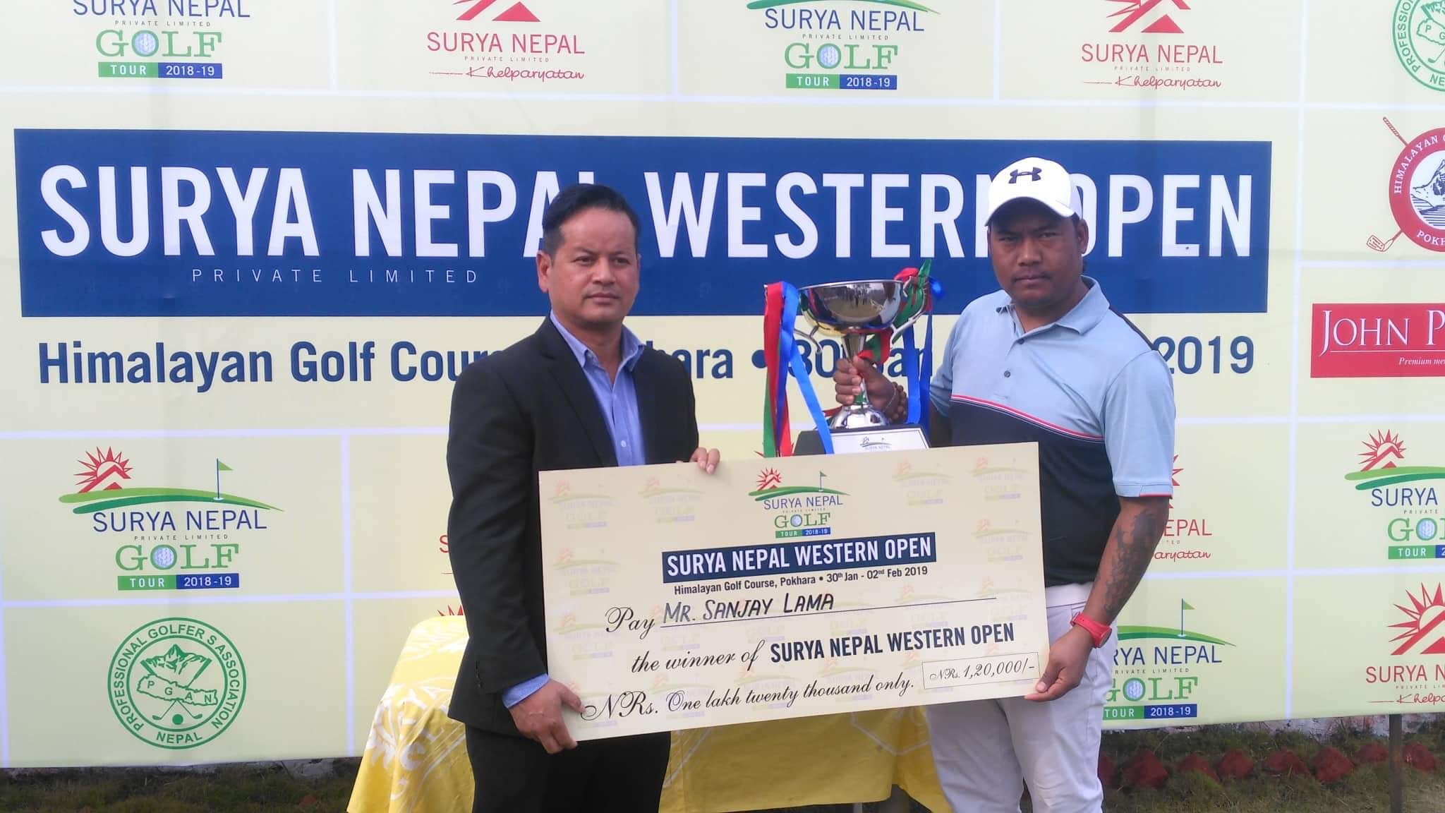 Brand Manager of Surya Nepal Pvt Ltd Keshav Pradhan handing over the trophy and cheque to Sanjay Lama (right) after the Surya Nepal Western Open at the Himalayan Golf Course in Pokhara on Friday. Photo: THT