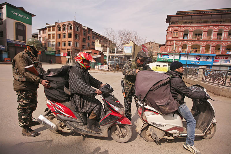 Indian Central Reserve Police Force (CRPF) personnel check the bags of scooterists during restrictions after Kashmiri separatist called for shutdown to protest the arrest of their leaders in Srinagar February 24, 2019. Photo: Reuters