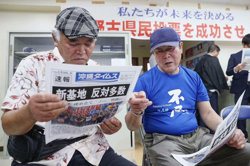 People take a look at a copy of a local newspaper reporting a referendum in Naha, Okinawa, Japan, Sunday, February 24, 2019. Photo:  Kyodo News via AP