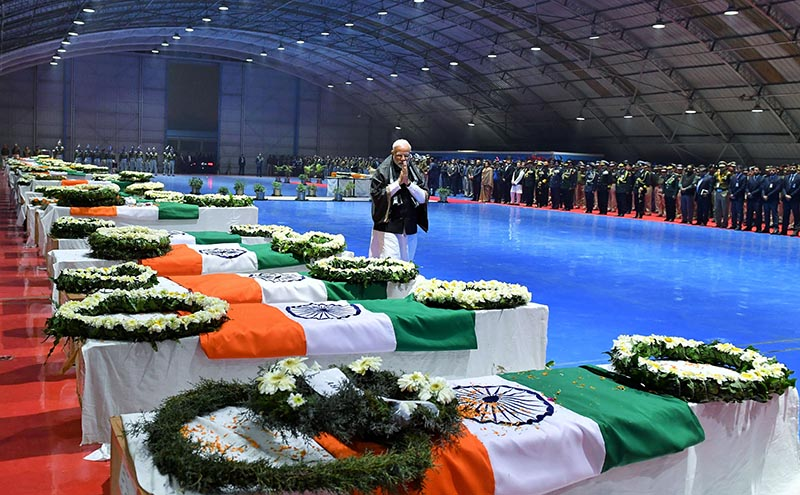 India's Prime Minister Narendra Modi pays tribute as he walks next to the coffins containing the remains of Central Reserve Police Force (CRPF) personnel who were killed after a suicide bomber rammed a car into a bus carrying them in south Kashmir on Thursday, at Palam airport in New Delhi, India, February 15, 2019. Photo: India's Press Information Bureau/Handout via Reuters