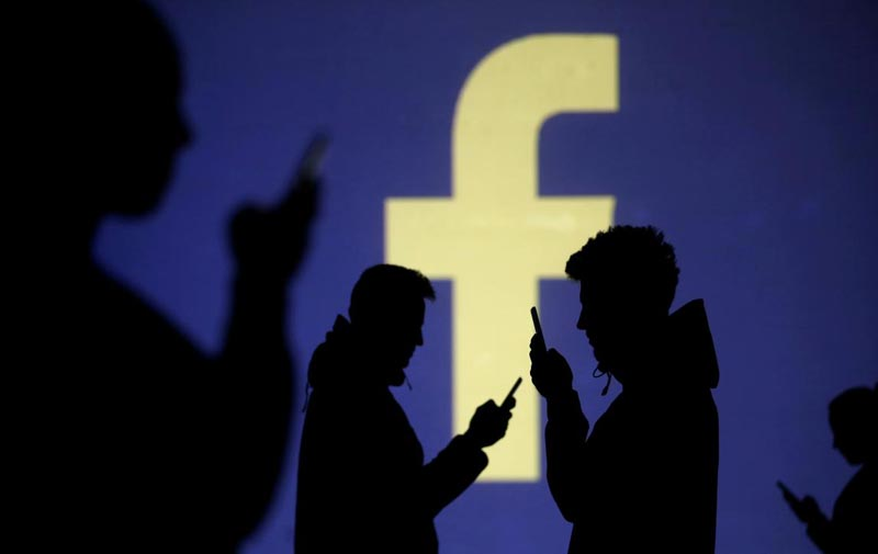 FILE PHOTO: Silhouettes of mobile users are seen next to a screen projection of Facebook logo in this picture illustration taken March 28, 2018. Photo: Dado Ruvic/REUTERS