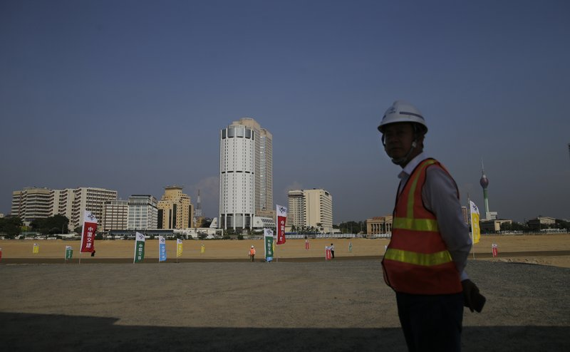 FILE - In this Jan. 2, 2018 file photo, a Chinese construction worker stands on land that was reclaimed from the Indian Ocean for the Colombo Port City project, initiated as part of China's ambitious One Belt One Road initiative, in Colombo, Sri Lanka. Photo: AP
