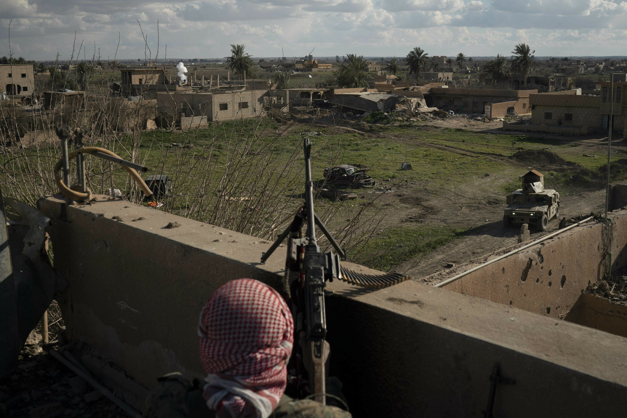 A US-backed Syrian Democratic Forces (SDF) fighter stands atop a building used as a temporary base near the last land still held by Islamic State militants in Baghouz, Syria, on Monday, Feb. 18, 2019. Photo: AP