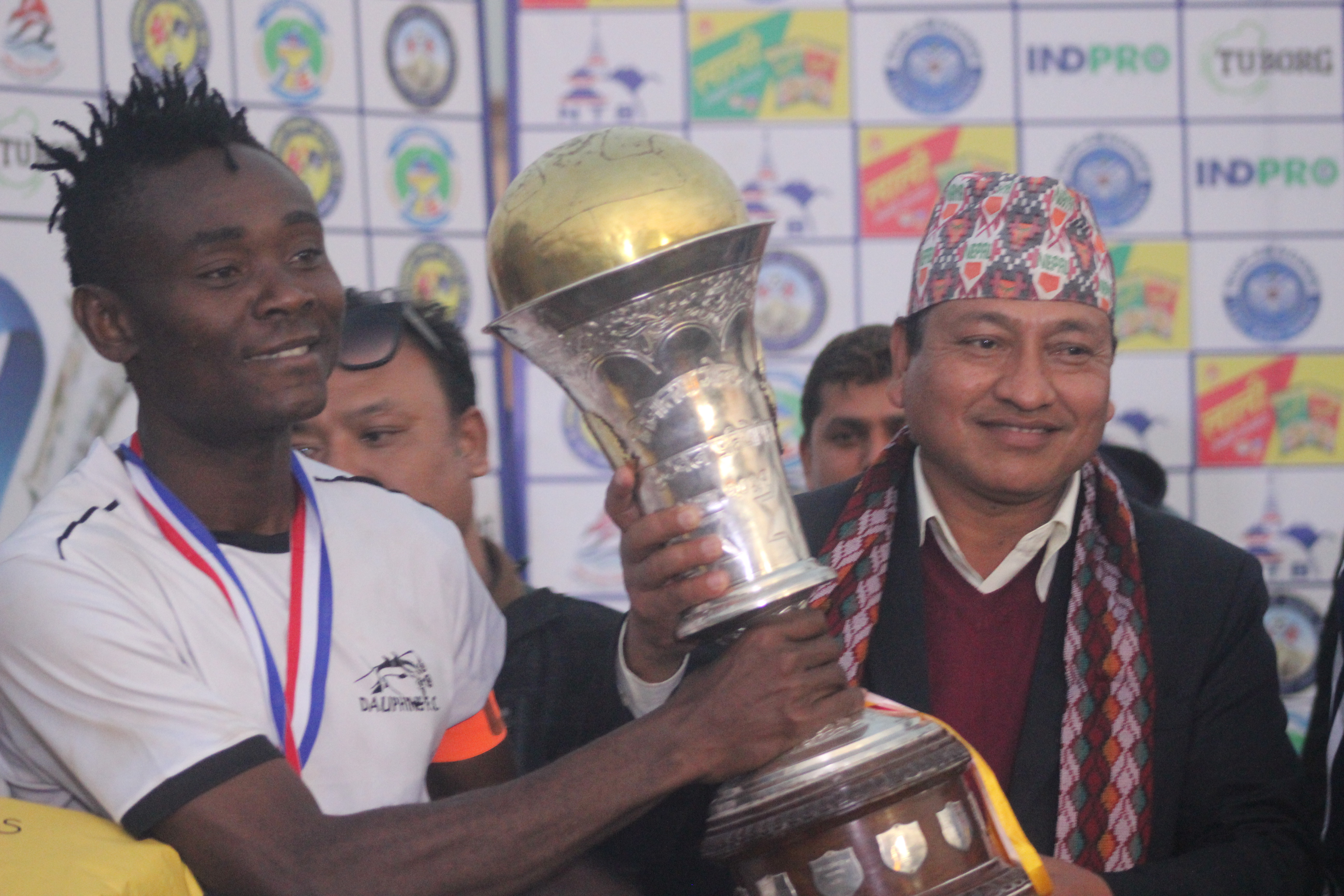 NSC Member Secretary Keshab Kumar Bista handing over the trophy to Dauphins Family Club player after the 21st Tilottama Gold Cup in Butwal on Monday. Photo: THT