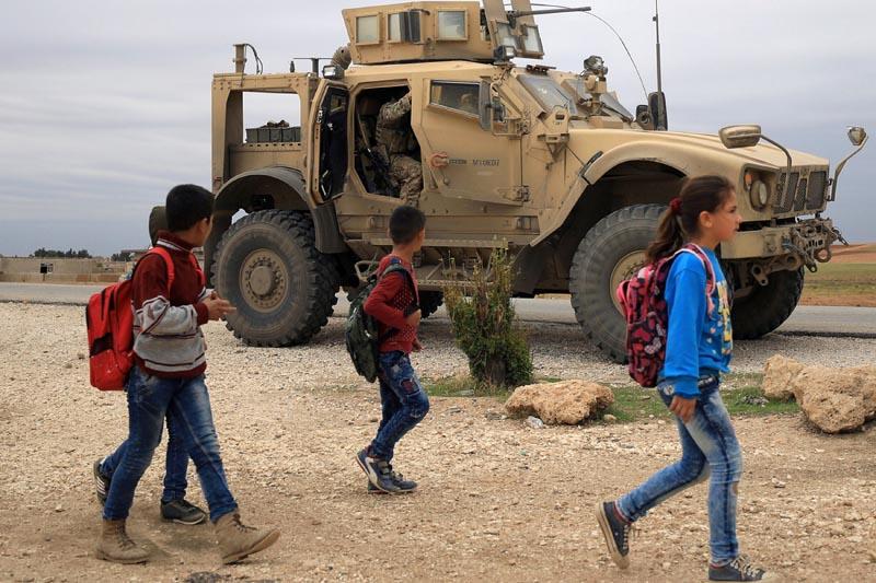 FILE: Syrian schoolchildren walk as US troops patrol near Turkish border in Hasakah, Syria November 4, 2018.Photo: Reuters/file