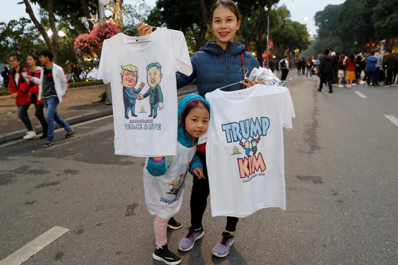 A girl stands next to a woman selling t-shirts depicting North Korea's leader Kim Jong Un and US President Donald Trump ahead of the summit in Hanoi, Vietnam February 23, 2019.Photo: Reuters