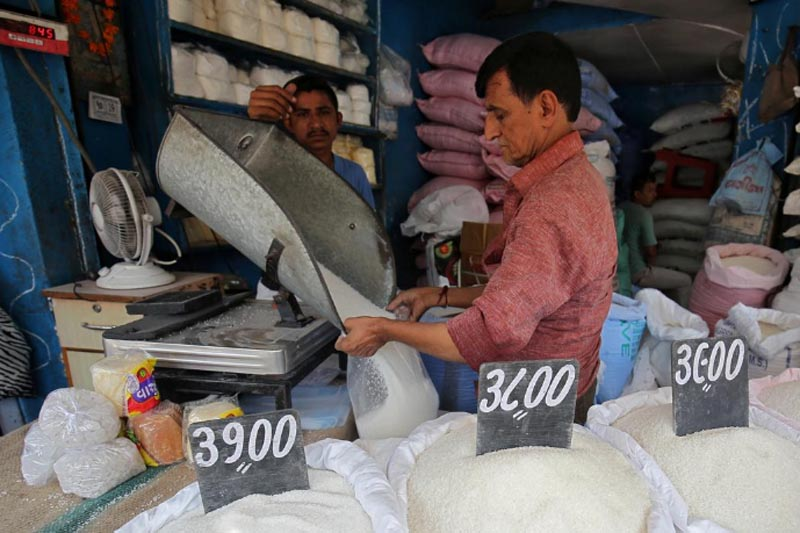 FILE: A man packs sugar for sale inside a shop at a marketplace in Ahmedabad, India, September 19, 2018.Photo: Reuters/file