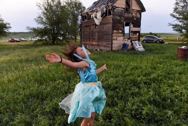 One of Beatrice Lookinghorse's granddaughters, Rozelynn Whitebull, plays near an abandoned house in the backyard of Beatrice Lookinghorse's trailer on the Cheyenne River Reservation in Green Grass, South Dakota, US, on May 31, 2018. Photo: Reuters