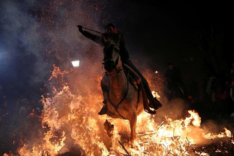 A woman rides a horse through flames during the annual