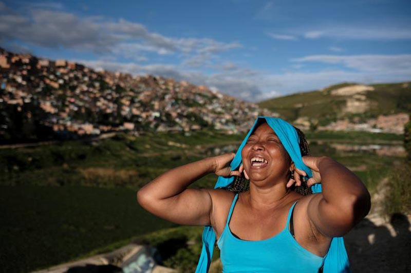 Lina, who said she was raped by dozens of right-wing paramilitary fighters in the Montes de Maria region during the five-decade civil war, laughs as she puts on a hairband in Soacha, on the outskirts of Bogota, Colombia, on June 12, 2018. Photo: Reuters