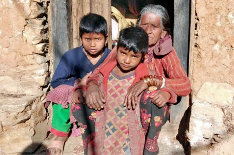 Two siblings along with their grandmother pose for a portrait infrong of their house in Bajura district, on Monday, March 04, 2019. Photo: Prakash Singh/THT