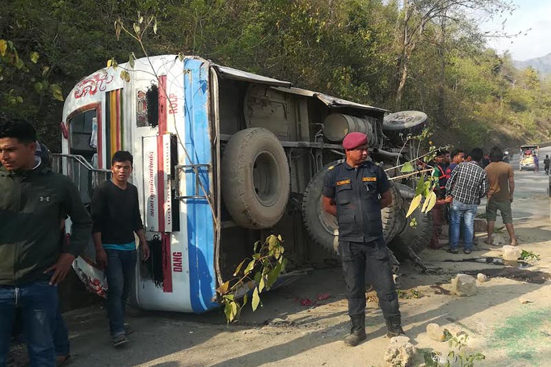 A security person standing at the site where a bus overturned on its side at Bagale of Ghorahi sub-metropolis, Dang, on Monday, March 18, 2019. Photo: THT