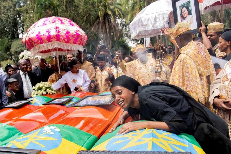 A woman mourns next to coffins during the burial ceremony of the Ethiopian Airline Flight ET 302 crash victims at the Holy Trinity Cathedral Orthodox church in Addis Ababa, Ethiopia, March 17, 2019. Photo: Reuters