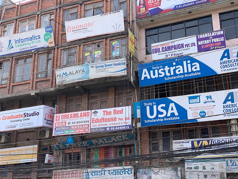 Hordes of billboards precariously perched on the walls of buildings in Putali Sadak, Kathmandu, on Wedmesday, March 27, 2019. Photo: Skanda Gautam/THT
