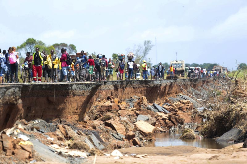 People pass through a section of the road damaged by Cyclone Idai in Nhamatanda about 50 kilometres from Beira, in Mozambique, Friday March, 22, 2019. Photo: AP