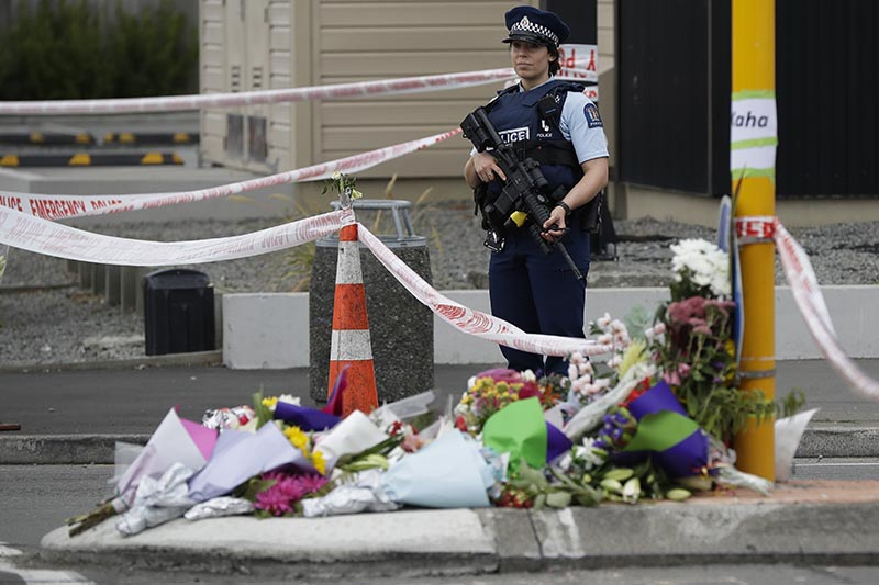 Police stand by makeshift memorial near the Linwood Mosque in Christchurch, New Zealand, on Saturday, March 16, 2019, where one of the two mass shootings occurred. Photo: AP