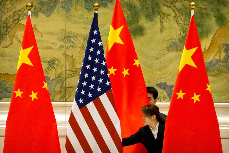 Chinese staffers adjust US and Chinese flags before the opening session of trade negotiations between US and Chinese trade representatives at the Diaoyutai State Guesthouse in Beijing, Thursday, February 14, 2019. Photo: Mark Schiefelbein/Pool via Reuters/File